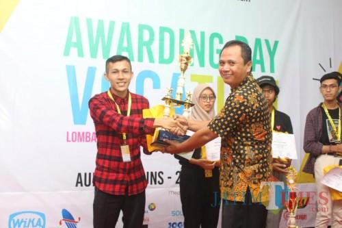 Muhammad Ali, mahasiswa Unikama yang menjuarai lomba vlog, saat menerima piala juara dari panitia. (Unikama for MalangTIMES)