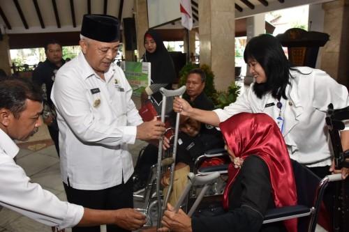 Bupati Malang HM Sanusi (tengah pakai peci) saat menyerahkan bantuan sosial kepada kaum difabel saat menghadiri agenda peringatan HKSN