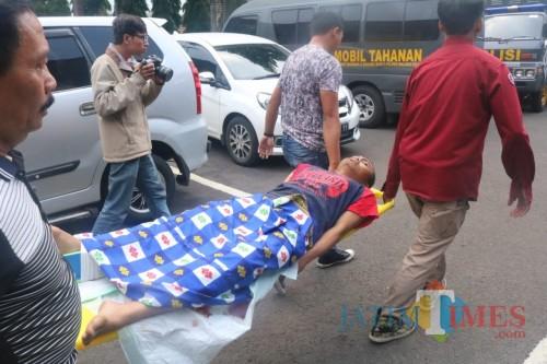 Kondisi tersangka Nur Kholis saat ditandu oleh petugas kepolisian di Polresta Malang  Kota. (Arifina Cahyanti Firdausi/MalangTIMES)