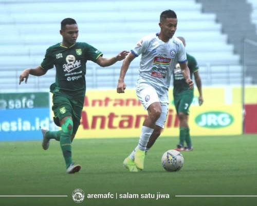 Dendi Santoso (putih) mendapatkan pengawalan ketat dari pemain Persebaya (official Arema FC)