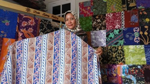 Owner Batik Lintang, Ita Fitriyah ST dan batik hasil karyanya bermotif Bunga Tlogosari (Pipit Anggraeni/ MalangTIMES).