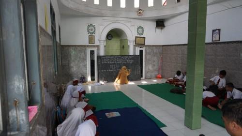 Sejumlah siswa mengikuti kegiatan belajar mengajar di musala.