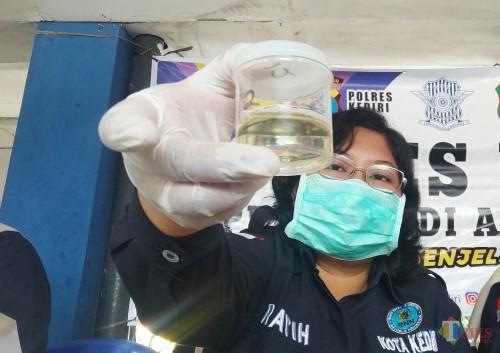 Petugas BNN Kota Kediri saat menunjukkan sempel urine. (eko Arif s /JatimTimes)