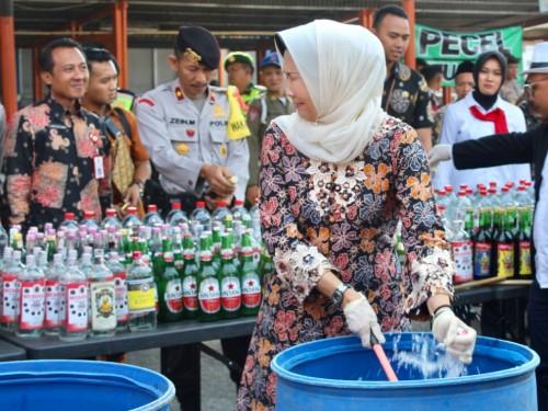 Wali Kota Batu Dewanti Rumpokosaat memecahkan botol minuman keras dihalaman Plaza Batu, Kecamatan Batu,Kamis (19/12/2019).