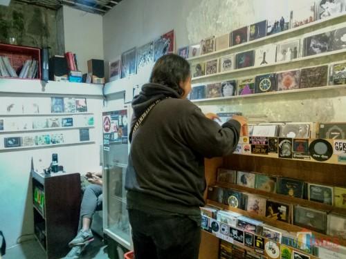 Salah satu pelanggan Toko Rekam Jaya sedang memilih CD. (Foto: Imarotul Izzah/MalangTIMES)