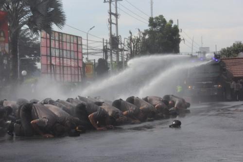 Tampak para polisi tengah sujud disemprot water canon. (ist)
