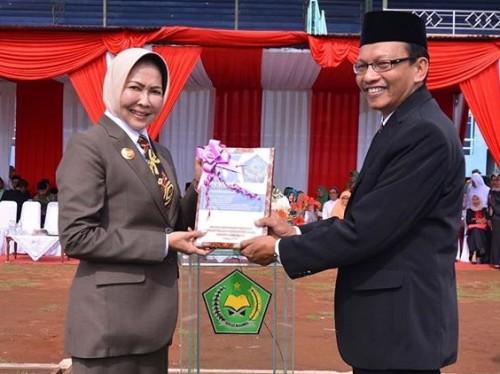 Kepala Kemenag Nawawi saat memberikan buku pedoman GERAMM kepada Wali Kota Batu Dewanti Rumpoko di Stadion Brantas.