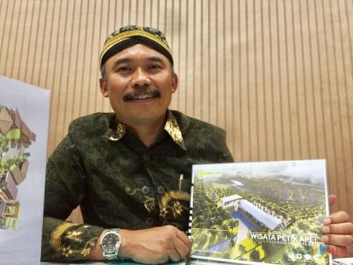 Kepala Desa Tulungrejo, Suliyono saat menunjukkan desain pembangunan Kebun Apel di Kantor Desa Tulungrejo (Foto: Irsya Richa/MalangTIMES)