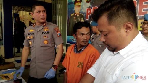 Samsul Arifin (tengah baju orange) saat ditunjukkan ke media oleh Kapolres Jember (foto : Moh. Ali Makrus / JatimTIMES)
