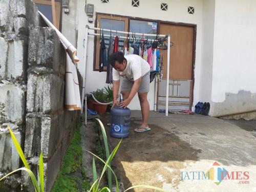 Salah satu warga yang terdampak air mati saat sedang mengisi air dari fasilitas perumahan. (Arifina Cahyanti Firdausi/MalangTIMES)