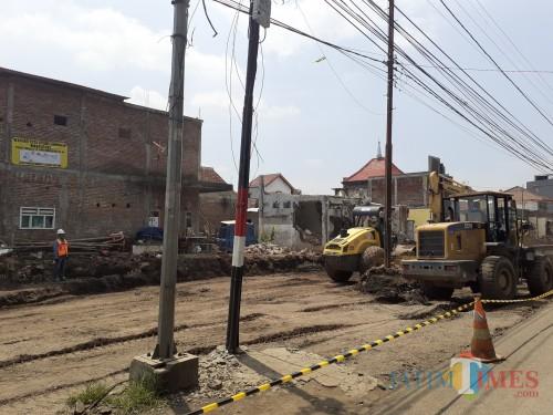 Alat berat dan aktivitas petugas di area pembangunan exit tol Madyopuro. (Arifina Cahyanti Firdausi/MalangTIMES)