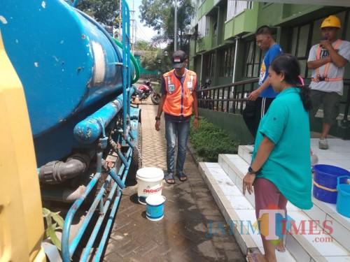 Warga Rumah Susun Sederhana Sewa (Rusunawa) Buring II saat mengantre untuk mengambi air dari tangki Perumda Tugu Tirta Kota Malang (Arifina Cahyanti Firdausi/MalangTIMES)