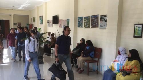 Terdakwa pembunuh begal (seragam abu-abu pakai topi dan masker) saat menuju ruang persidangan (Foto : Ashaq Lupito / MalangTIMES)