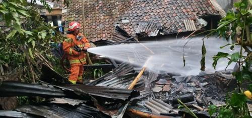 Petugas saat melakukan pendinginan di lokasi kebakaran rumah Atim di alan Wukir RT 05 RW 04, Kelurahan Temas, Kecamatan Batu, Jumat (24/1/2020). (Foto: istimewa)
