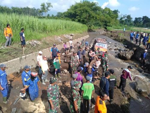 Petugas gabungan beserta warga saat membersihkan sisa material banjir bandang