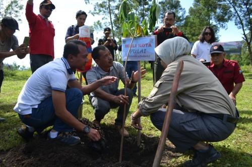 Wali Kota Batu Dewanti Rumpoko saat menanam bibit pohon di area Perhutani Kawasan Penangkaran Kuda Megastar, Desa Oro-Oro Ombo, Kecamatan Batu, Jumat (31/1/2020).