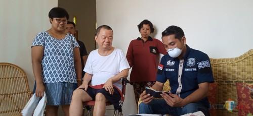 Denny Irawan (baju biru) saat memeriksa dokumen kependudukan Lai Chin Cheung (baju putih) (Joko Pramono for Jatim Times)