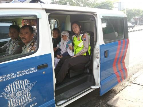 Terlihat nampak anggota Dikyasa Polresta Malang Kota mengantarkan dua anak yang nyaris saja tak bisa berangkat sekolah karena motor sang ayah yang mengalami ban kempes (Ist)