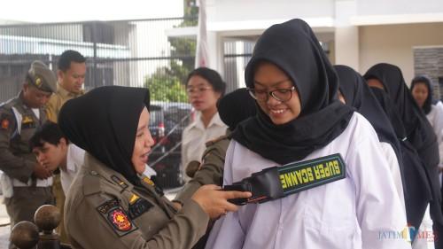 Salah seorang peserta diperiksa menggunakan metal detektor oleh Satpol PP sebelum masuk ruang ujian (Joko Pramono for JatimTIMES)