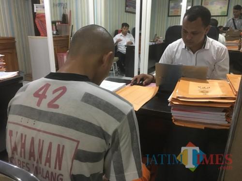 Tersangka AT saat diinterogasi penyidik Unit PPA (Pelayanan Perempuan dan Anak) Polres Malang. (Foto: Ashaq Lupito/MalangTimes)
