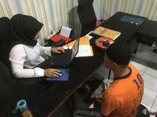 Atmari (baju tahanan warna oranye), tersangka persetubuhan anak di bawah umur saat dimintai keterangan di hadapan penyidik Unit PPA Satreskrim Polres Malang. (Foto : Ashaq Lupito / MalangTIMES)