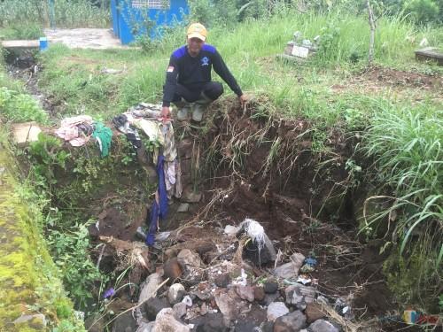 Salah satu relawan yang terlibat dalam proses pencarian saat menunjukkan lokasi kejadian tempat dimana balita diduga hanyut (Foto : Ashaq Lupito / MalangTIMES)