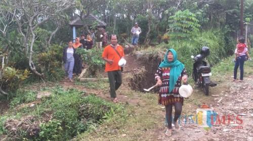 Para warga saat memukul peralatan dapur guna mencari keberadaan korban yang dikabarkan hanyut terbawa arus sungai sesaat setelah jatuh ke selokan (Foto : Ashaq Lupito / MalangTIMES)