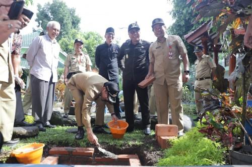 Proses pemasangan sumur injeksi yang turut dilakukan oleh Wali Kota Malang Sutiaji (pegang ember oeange) di Kecamatan Blimbing, Selasa (11/2) (Foto: Humas Pemkot Malang)