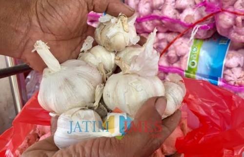 Seorang pedagang memegang bawang putih di Pasar unit sayur Kota Batu. (Foto: Irsya Richa/MalangTIMES)