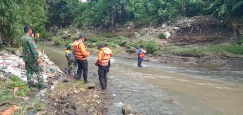 Petugas saat melakukan penyisiran guna mencari keberadaan balita yang diduga hanyut terbawa arus drainase saat banjir.