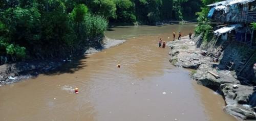 Petugas saat melakukan penyisiran guna mencari keberadaan balita yang diduga hanyut terbawa arus sungai.