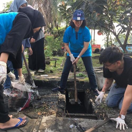 Kepala DLH Kota Malang Rinawati (kaus biru, bertopi) saat ikut turun ke lapangan untuk membersihkan selokan di Jalan Soekarno-Hatta. (DLH for malang times)