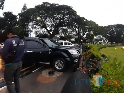 Numpak mobil yang menabrak tembok alun-alun Tugu Kota Malang (Arifina/MalangTIMES)
