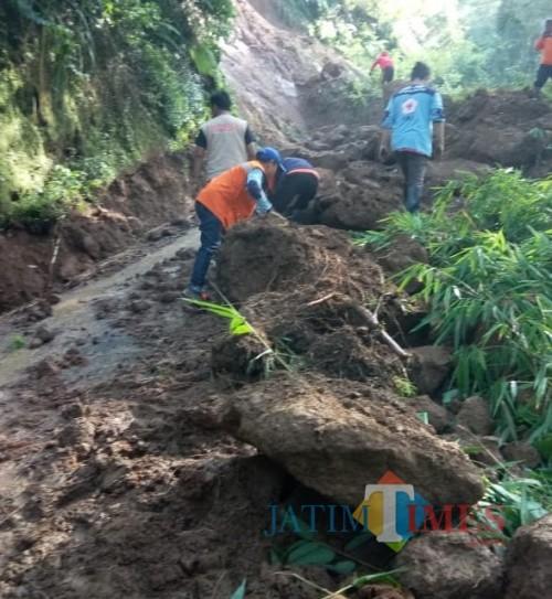 Petugas saat mengevakuasi material longsor yang menutup akses jalan antar dua desa di Kecamatan Pujon. (Foto: PMI Kabupaten Malang for MalangTIMES)