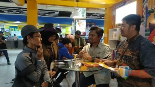 Petugas layanan Mandiri Syariah saat memeragakan pembukaan rekening online pada pengunjung (Arifina Cahyanti Firdausi/MalangTIMES)