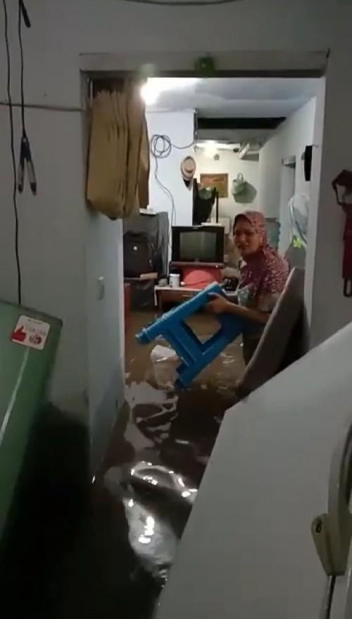 Nampak seorang ibu-ibu yang tengah menyelamatkan perabotannya yang terkena banjir (ist)