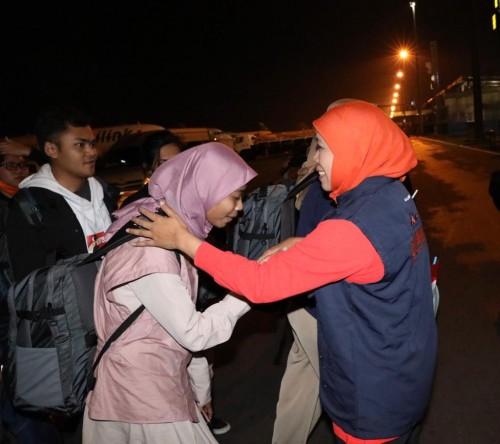Gubernur Jawa Timur Khofifah Indar Parawansa (jilbab orange) saat menyambut kedatangan 65 warga Jatim dari Natuna, Kepri, Sabtu malam (15/2) (Foto: istimewa)