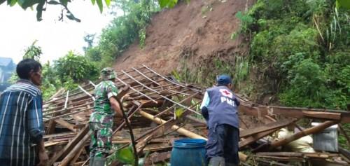 Petugas gabungan saat mengevakuasi sisa material longsor di lokasi kejadian