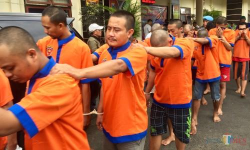 Para tersangka saat berbaris di Polres Batu, Jumat (21/2/2020). (Foto: Irsya Richa/MalangTIMES)