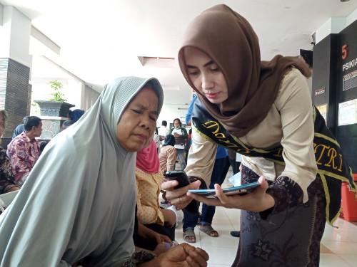 Duta bSi Poetri mengajarkan pada pasien untuk mendaftar menggunakan gawainya (Joko Pramono for JatimTIMES)