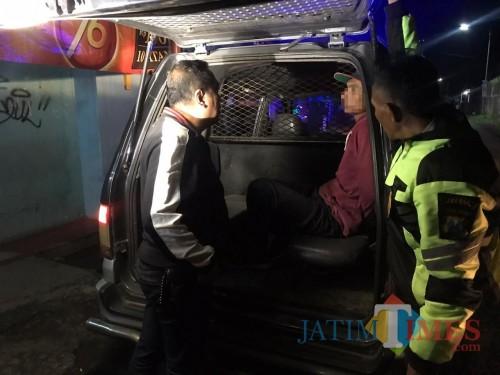 Tersangka Sudi Hartono alias Remon (di dalam mobil) saat digelandang petugas ke kantor Mapolsek Singosari