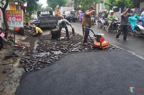 Petugas DPUPRPKP  tengah melakukan perbaikan jalan aspal yang mengelupas di Jalan Bandulan. (Anggara Sudiongko/MalangTIMES)