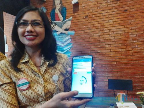 Kepala BPJS Cabang Malang Dina Diana Permata saat menunjukkan cara penggunaan fiture antrean online melalui aplikasi JKN. (Arifina Cahyanti Firdausi/MalangTIMES)