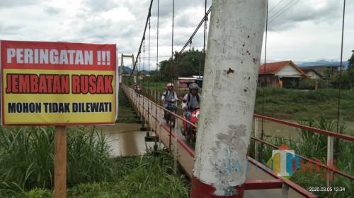 nekat, sejumlah pelajar dan masyarakat tetap melewati jemabtan itu meski sudah ada papan larangan untuk melewati jembatan itu (Joko Pramono/ JatimTIMES)