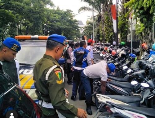 Petugas operasi gabungan saat gembosi kendaraan roda dua yang parkir di area terlarang di Jl. Veteran (Istimewa).