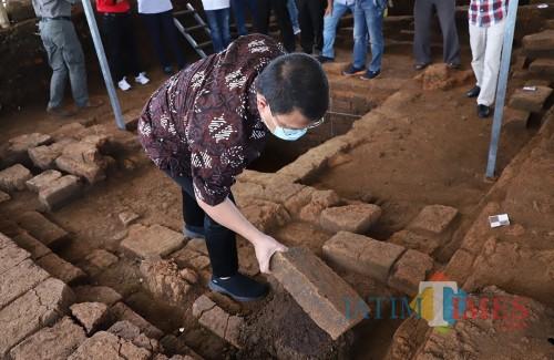 Wakil MPR RI Ahmad Bashara saat memegang batu bata temuan situs di Dusun Pendem, Desa Pendem, Kecamatan Junrejo, Minggu (15/3/2020).