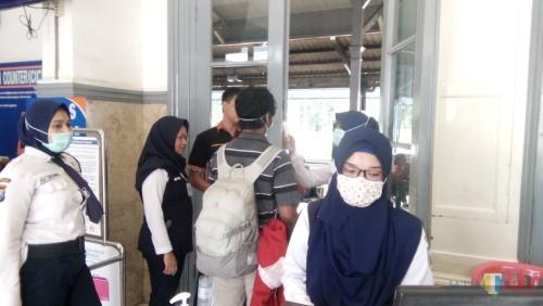 Calon penumpang PT KAI saat dicek suhu tubuhnya sebelum masuk ke ruang boarding stasiuun (foto : Moh. Ali Makrus / Jatim TIMES)
