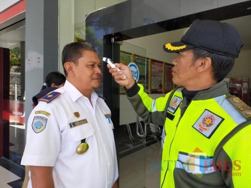 Salah satu petugas sedang memeriksa kepala Dinas Perhubungan di Balai Kota Among Tani, Senin (16/3/2020). (Foto: Muklas/JatimTIMES)
