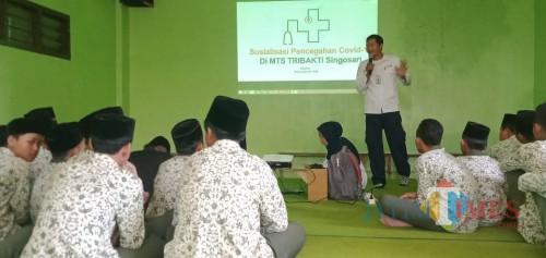 PMI Kabupaten Malang Unit Singosari sedang melakukan sosialisasi pencegahan covid-19 di MTs Tribakti Singosari.