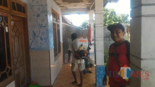 Kades Olehsari Joko Mukhlis mendampingi warga lakukan penyemprotan disinfektan. (Nurhadi Banyuwangi/Jatim TIMES)